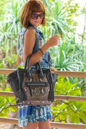 Fashion portrait of pretty young caucasian woman with handmade snakeskin python handbag. Sunny day on a tropical Bali island. Stock Photo