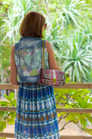 Fashion portrait of pretty young caucasian woman with handmade snakeskin python handbag. Sunny day on a tropical Bali island. Stock Photo