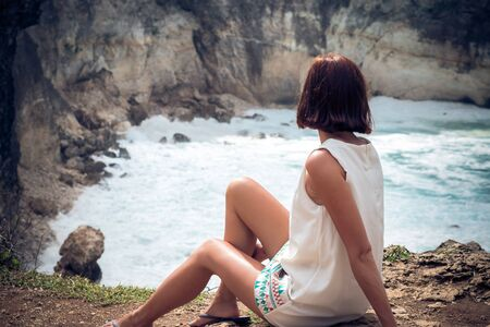Freedom young caucasian woman sitting and posing on mountain peak rock, cliff. Beautiful blue ocean on the background. Tropical island Nusa Lembongan, Bali, Indonesia, Asia. Rare view. Stock Photo