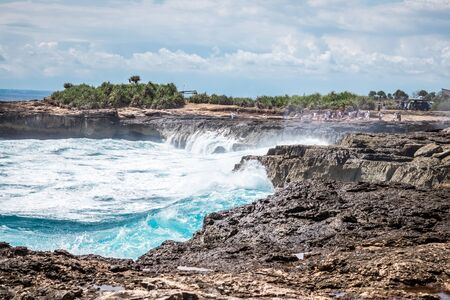 A beautiful blue wave crashes down at the rocks in Devils Tear, tropical island Nusa Lembongan, Indonesia. Sunny day, big waves.