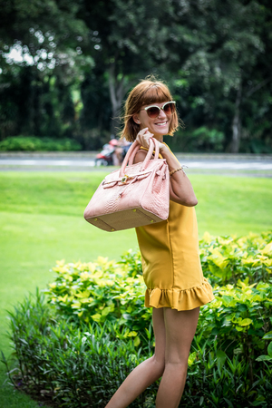 Portrait of a Beautiful fashionable caucasian brunette woman with sunglasses and luxury snakeskin python handbag posing in the park of Nusa Dua, Bali, Indonesia. Asia. Sunny day, green background.
