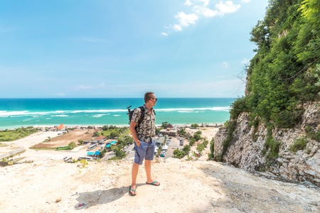 Handsome traveler man stay by blue ocean background - Happy guy relaxing at sea view point - Concept of freedom and summer trip around the world backpacker style. Bali, Indonesia.