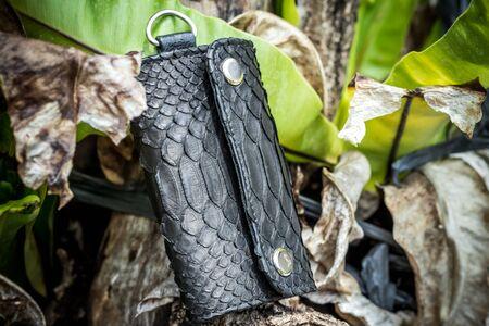 Leather Keychain, handmade snakeskin python. Bali island. Green and wooden background.