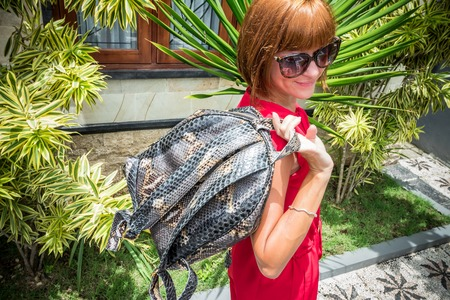 Stylish young woman in red dress with leather snakeskin python rucksack in the asian garden. Tropical Bali island, handmade snakeskin luxury backpack.