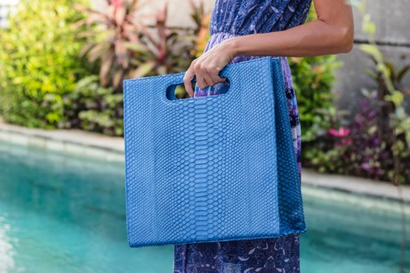 Fashionable beautiful big blue snakeskin python handbag on the arm of the girl in a fashionable dress, posing near the swimming pool on a warm summer night. Warm color. Stock Photo