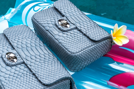Woman luxury snakeskin python handbag in the swimming pool. Handmade luxury bag.