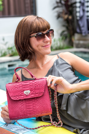 Fashionable woman holding luxury stylish snakeskin python bag. Elegant outfit. Close up of purse in hands of stylish lady. Model posing neat the swimming pool. Female fashion.