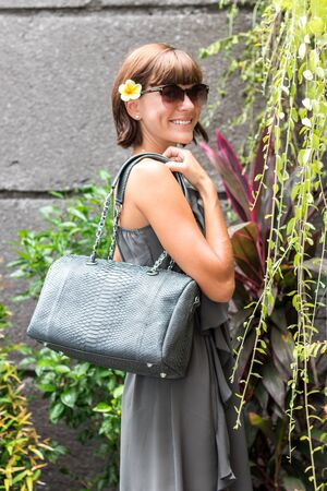 Fashionable woman holding luxury stylish snakeskin python bag. Elegant outfit. Close up of purse in hands of stylish lady. Model posing. Female fashion. Stock Photo