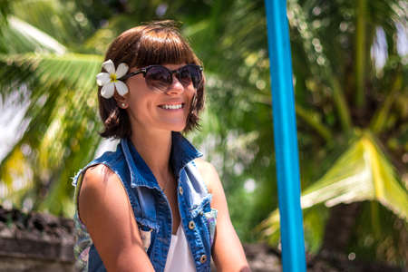 Portrait Young beautiful tropical woman on summer vacation in asia, Bali. Relaxing on tropical beach, sea landscape and gree tropical background, slim tanned body, travel alone, short hair.