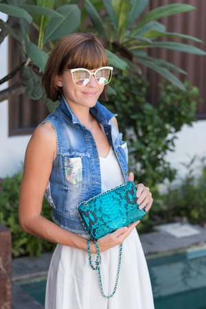 Young stylish woman in trendy outfit with snakeskin python luxury bag in hands. Woman with handbag near the swimming pool.
