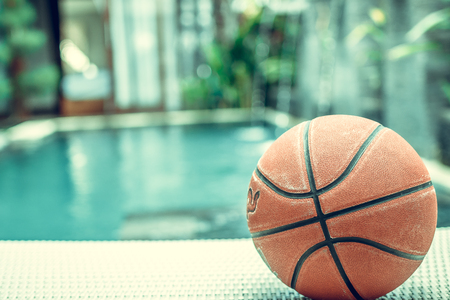 Basketball ball on a swimming pool background, tropical sport scene.