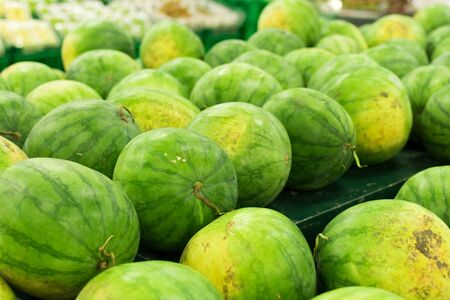 Many big sweet green watermelons sell on market. Local organic market on tropical Bali, Indonesia. Watermelon background. Stock Photo