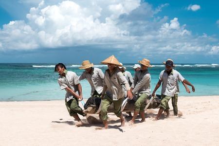 BALI, INDONESIA - APRIL 26, 2017: Paradise beach workers bringing a big tree on Bali island.