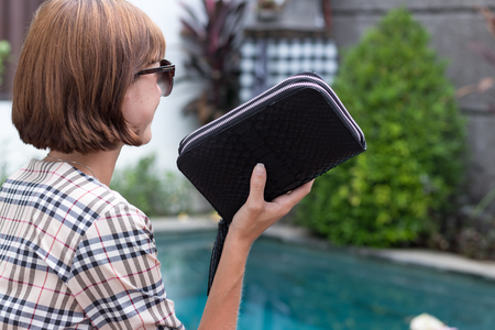 Fashion luxury snakeskin python wallet in woman hands sitting near the swimming pool, Bali.