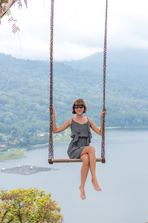 Sexy young aldy swinging over the precipice on the magic tropical Bali island, Indonesia.