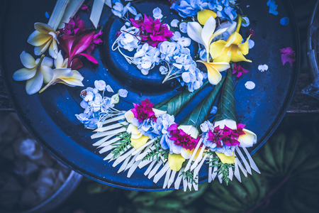 Offerings to gods in Bali with flowers. Exotic tropical Bali island, Indonesia. Stock Photo