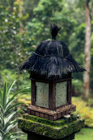 Wooden balinese lamp outdoors in the jungle rainforest of Bali island, Indonesia. Tropical background. Vintage asian lamp.