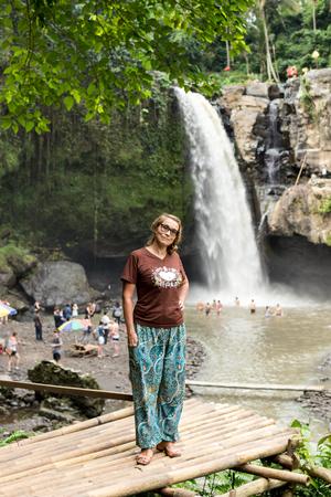 ubud: Woman on a waterfall deep in the tropical rain forest of Ubud, tropical Bali island, Indonesia. Exotic scene of tropics. Stock Photo