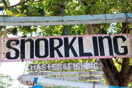 Wooden plate with text snorkling on the Sanur beach, tropical island Bali, Indonesia.