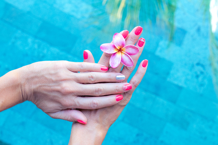 arm bouquet: Plumeria frangipani flower in woman hand on a swimming poolbackground Stock Photo