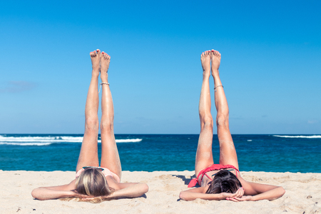 nusa: Two happy sexy women friends sunbathing on the tropical beach of Bali island, Nusa Dua, Indonesia.