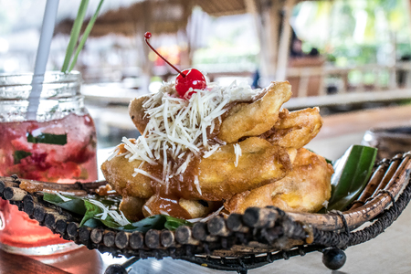 Fried banana desser, pisang goreng keju, indonesian dessert with batter fried bananas dusted with powdered sugar and cheese.
