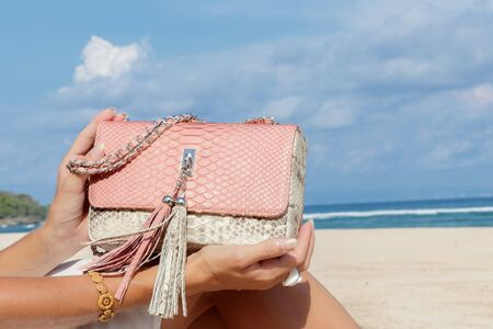 Close-up young woman hands with luxury expensive snakeskin python handbag. Indian ocean on a background.