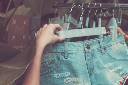 clothing store: Woman new jeans shorts. New jeans shorts on showcase. Jeans shorts for ladies. Short shorts for women. Woman shopping on Bali island.