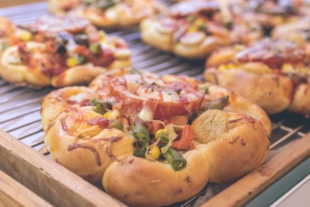 cutting: Mini pizzas with cheese, tomato, green beans, corn and sausages in the shoppin mall, small italian bakery. Tropical island of Bali, Indonesia. Stock Photo