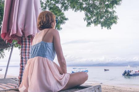 nusa: Woman sitting on beach in deck chair on a cloudy day. Nusa Lembongan island, Bali, Indonesia.