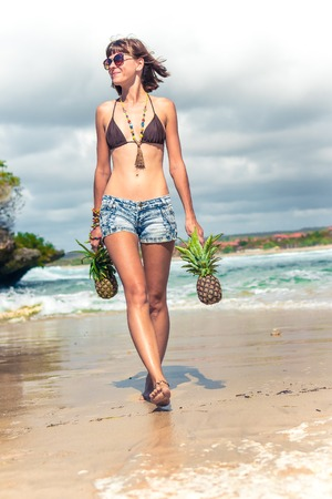 Tropical summer woman with pineapple walking on the beach. Outdoors, ocean, nature. Bali island paradise.