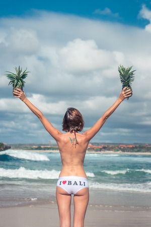 Sexy tropical woman butt close up with exotic pineapple fruit on the beach of paradise island of Bali. Healthy diet concept. I love Bali. Stock Photo
