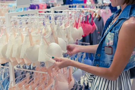 hangers: Woman chooses a brassiere in a shopping mal of tropical island Bali, Indonesia. Stock Photo
