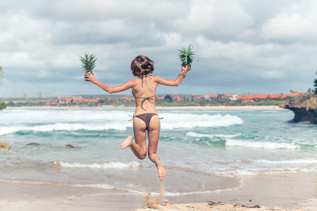 Sexy young lady in bikini jumping on the beach with fresh raw healthy pineapple fruit. Happy vacation concept. Bali.