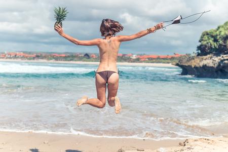 Sexy jeune femme en bikini, sauter sur la plage avec des fruits d'ananas sains et crus. Concept de vacances heureux. Bali. Banque d'images - 83491444