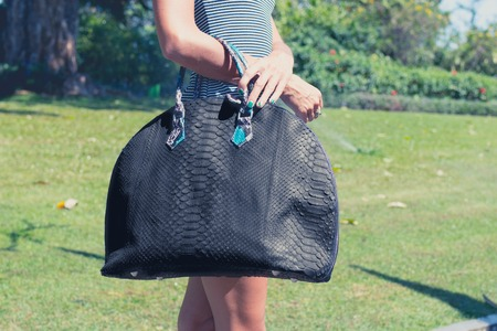 Woman with a big luxury snakeskin fashion python bag in the park of Nusa Dua, Bali island.