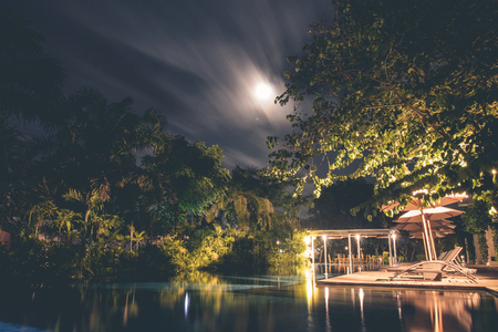 bedchamber: Swimming pool in luxury modern resort with tropical garden at night time.