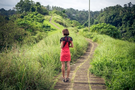 Young sexy woman in red dress in the tropical landscape of Bali island. Woman having summer vacation and enjoy paradise.