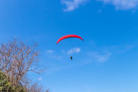Raraplane flying in the beautiful sky. Tropical Bali island, Indonesia. Extreme sport.