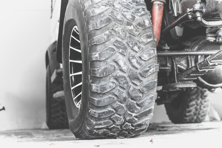 Close up of dirty car wheel on the road. Bali island.
