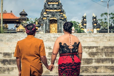 Lovely honeymoon balinese couple in traditional clothes together at the balinese temple. Bali island. Asia.