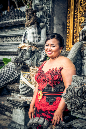 Close up portrait of traditionally dressed young female Balinese woman at the temple. Bali.
