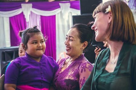BALI, INDONESIA - OCTOBER 23, 2017: Woman and kid on Wedding ceremony, balinese wedding.