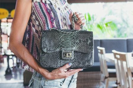 Closeup woman hands with fashion luxury snakeskin python handbag. Outdoors.