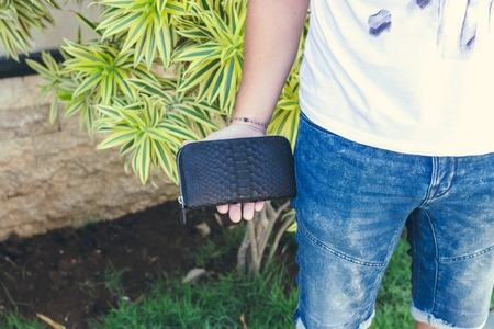 Man holding handmade purse made from exotic leather snakeskin python, outdoors, green tropical background.