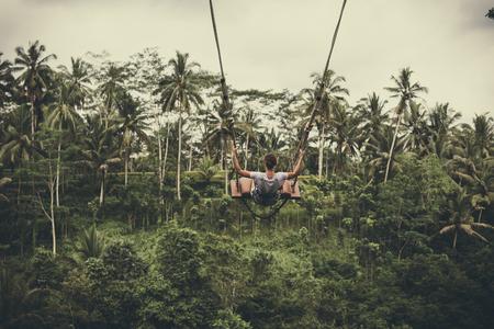 젊은 관광 여자 열 대 발리 섬의 정글 열대 우림에 절벽에 스윙. 스톡 콘텐츠