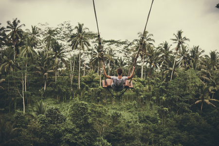 Young tourist woman swinging on the cliff in the jungle rainforest of a tropical Bali island.