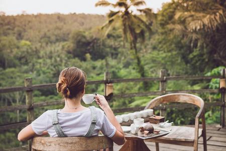 Prueba de café de la mujer joven durante puesta del sol en la selva tropical de la selva de una isla tropical de Bali. Foto de archivo