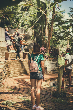 BALI, INDONESIA - DECEMBER 5, 2017: Woman looking on Group of Men helping a tourist sit down on a swings on the cliff. Tropical Bali island, Indonesia.