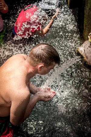 BALI, INDONESIA - DECEMBER 5, 2017: Holy spring water. People praying in the Tirta Empul temple. Bali. Editorial
